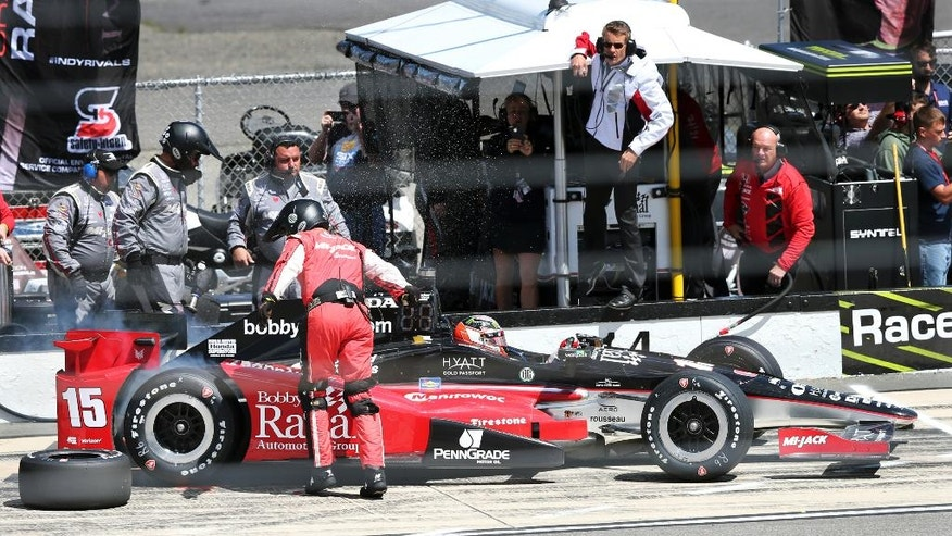A crew member leaps out of the way as Graham Rahal (15) leaves after a pit stop during the Pocono IndyCar 500 auto race Monday, Aug. 22, 2016, in Long Pond, Pa. (AP Photo/Mel Evans)