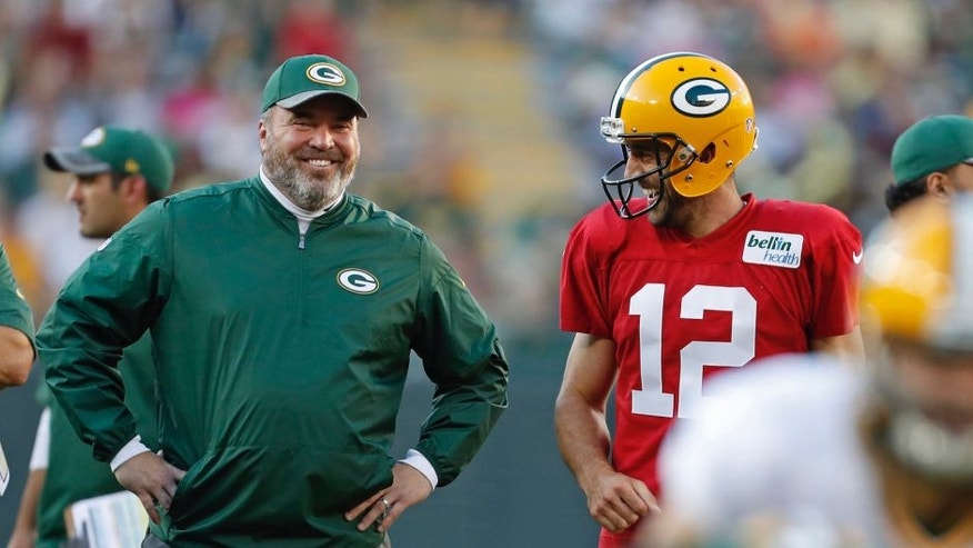 <p>Green Bay Packers quarterback Aaron Rodgers and head coach Mike McCarthy share a laugh during training camp, Sunday, July 31.</p>