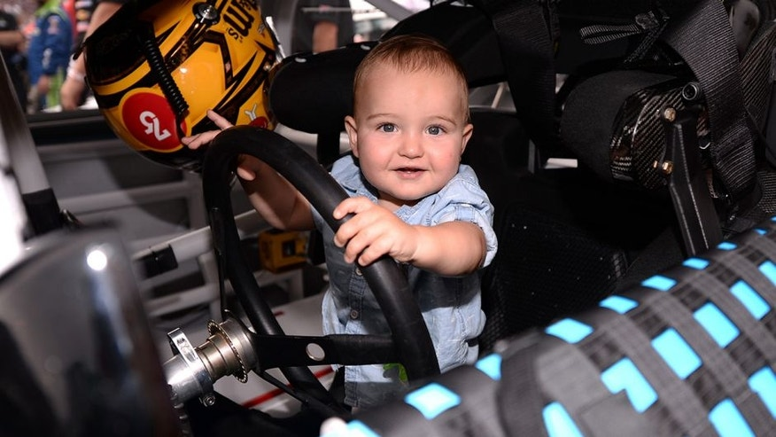CHARLOTTE, NC - MAY 29: Brexton Busch, son of Kyle Busch, driver of the #18 M&M's Toyota, stands in the #18 car prior to the start of the NASCAR Sprint Cup Series Coca-Cola 600 at Charlotte Motor Speedway on May 29, 2016 in Charlotte, North Carolina. (Photo by Blaine Ohigashi/Getty Images)