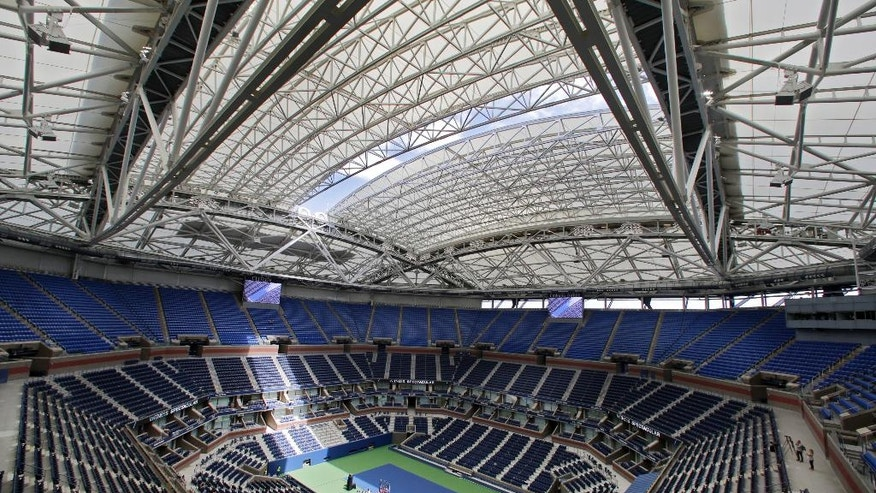 FILE - In this Aug. 2, 2016, file photo, the partially open new retractable roof allows a ribbon of light into Arthur Ashe Stadium at the Billie Jean King National Tennis Center, in the Queens borough of New York. The first round of the U.S. Open tennis tournament is scheduled for Monday, Aug. 29. (AP Photo/Richard Drew, File)