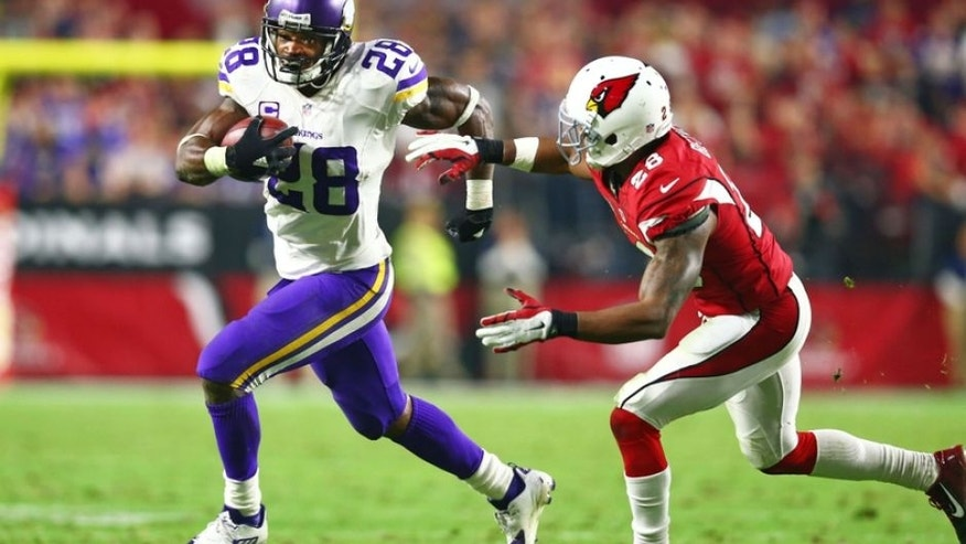 Dec 10, 2015; Glendale, AZ, USA; Minnesota Vikings running back Adrian Peterson (left) runs the ball against Arizona Cardinals cornerback Justin Bethel in the fourth quarter at University of Phoenix Stadium. The Cardinals defeated the Vikings 23-20. Mandatory Credit: Mark J. Rebilas-USA TODAY Sports