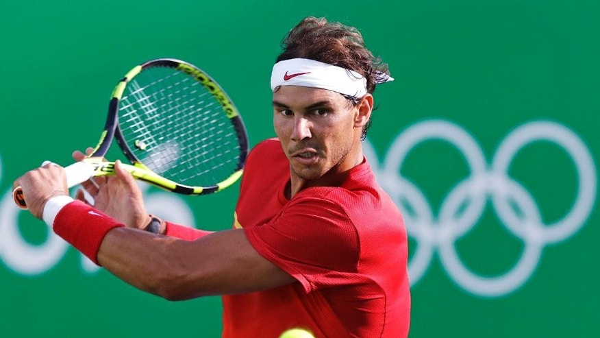 FILE - In this Aug. 12, 2016, file photo, Rafael Nadal, of Spain, returns during his match against Thomaz Bellucci, of Brazil, during their quarterfinal round match at the 2016 Summer Olympics in Rio de Janeiro, Brazil. The U.S. Open tennis tournament begins Monday, Aug. 29.  (AP Photo/Charles Krupa, File)
