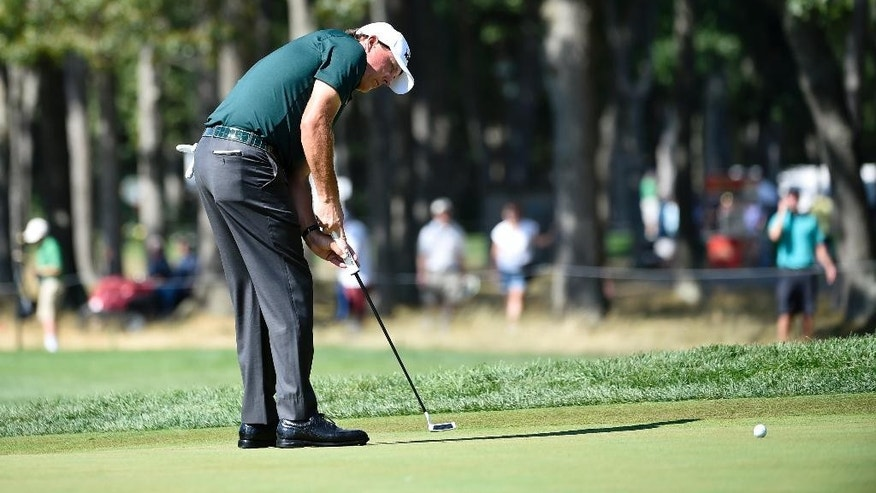 Phil Mickelson putts on the seventh green during the third round of the Barclays golf tournament in Farmingdale, N.Y., Saturday, Aug. 27, 2016. (AP Photo/Kathy Kmonicek)