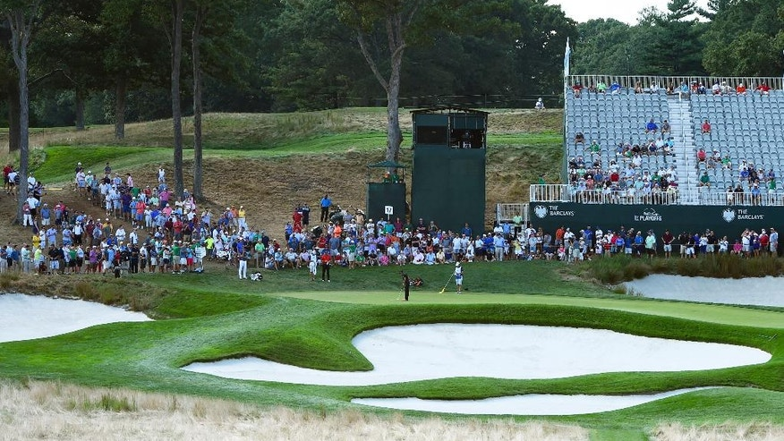 Spectators watch Rickie Fowler complete his putt on the 17th green during the second round of The Barclays golf tournament in Farmingdale, N.Y., Friday, Aug. 26, 2016, (AP Photo/Kathy Kmonicek)