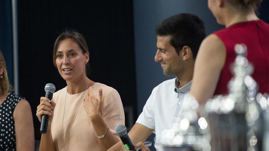 Reigning U.S. Open tennis women's singles champion Flavia Pennetta, of Italy, speaks as men's singles champion Novak Djokovic looks on during a media availability at the Billie Jean King National Tennis Center, Friday, Aug. 26, 2016,  in New York. (AP Photo/Bryan R. Smith)