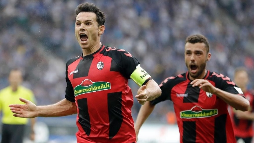 Freiburg's Nicolas Hoefler, left, celebrates after scoring his side's first goal during the German Bundesliga soccer match between Hertha BSC Berlin and SC Freiburg in Berlin, Germany, Sunday, Aug. 28, 2016. (AP Photo/Michael Sohn)