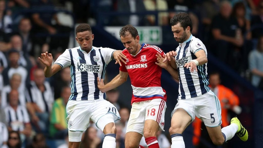 Middlesbrough's Christian Stuani, centre, is challenged by West Bromwich Albion's Brendan Galloway, left, and Claudio Yacob during their English Premier League soccer match at The Hawthorns, West Bromwich, England, Sunday, Aug. 28, 2016. (Nick Potts/PA via AP)