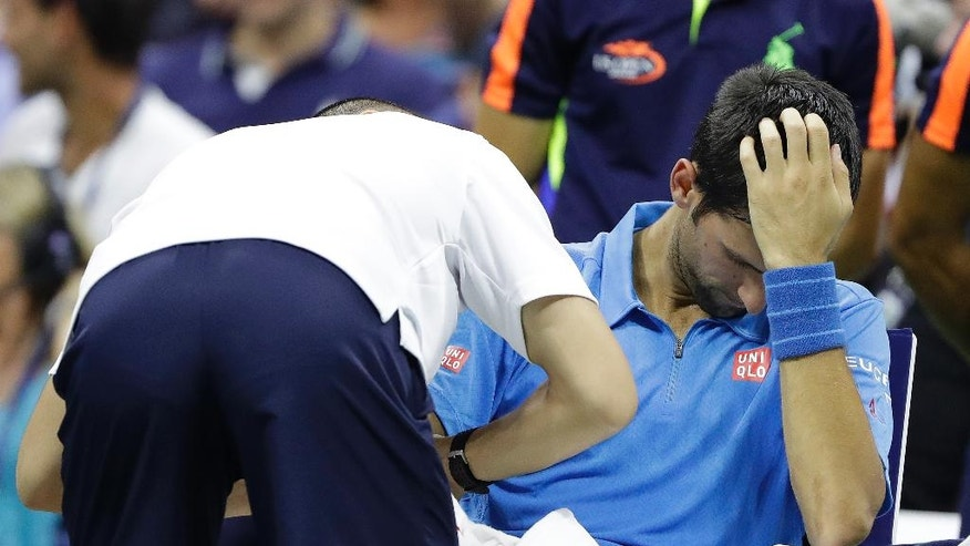 Novak Djokovic, of Serbia, get medical attention during his first round match against Jerzy Janowicz, of Poland, at the US Open tennis tournament, Monday, Aug. 29, 2016, in New York. (AP Photo/Darron Cummings)