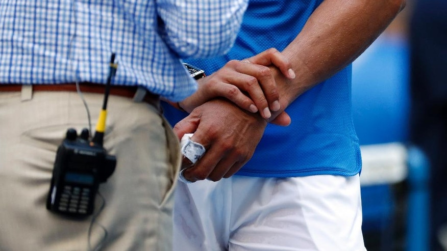 Rafael Nadal, of Spain, holds his left wrist while answering questions after defeating Denis Istomin, of Uzbekistan, during the first round of the U.S. Open tennis tournament, Monday, Aug. 29, 2016, in New York. (AP Photo/Alex Brandon)