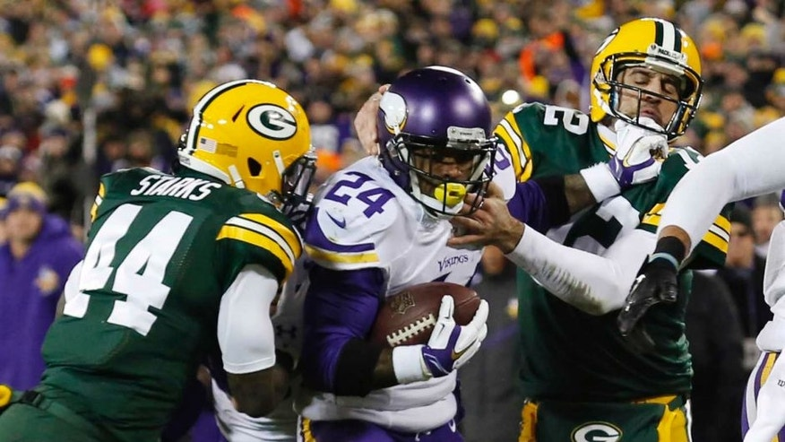 The Minnesota Vikings' Captain Munnerlyn (center) gets past the Green Bay Packers' Aaron Rodgers (right) and James Starks for a touchdown after recovering a fumble during the second half Sunday, Jan. 3, 2016, in Green Bay, Wis.