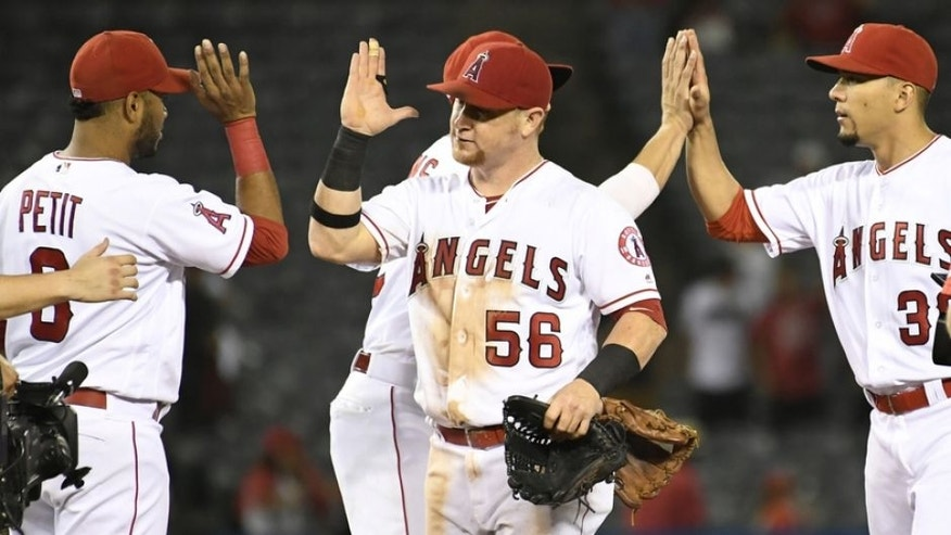 Aug 29, 2016; Anaheim, CA, USA; Los Angeles Angels right fielder Kole Calhoun (56) and teammates celebrate their 9-2 win over the Cincinnati Reds at Angel Stadium of Anaheim. Mandatory Credit: Richard Mackson-USA TODAY Sports