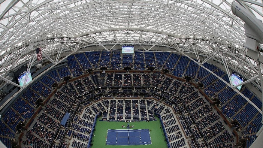 Simona Halep, of Romania, serves to Lucie Safarova, of the Czech Republic, during the second round of the U.S. Open tennis tournament, Thursday, Sept. 1, 2016, in New York. Despite rain falling outside Arthur Ashe Stadium, the new roof was closed to allow play to begin. (AP Photo/Julie Jacobson)
