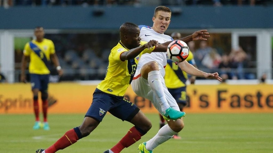 """FILE - In this June 16, 2016, file photo, United States' Matt Besler, right, and Ecuador's Enner Valencia vie for the ball during a Copa America Centenario quarterfinal soccer match in Seattle. Besler got back to the U.S. team hotel after training for a World Cup qualifier at St. Vincent and the Grendadines when his cell phone came back to life. """"I had a message from my wife just saying, call me ASAP, and I had that feeling that something was happening,"""" he said. Back in Kansas City, Kan., Amanda Besler felt her water break went into labor two weeks early. On a Caribbean island, there was no way Matt Besler could return home quickly. Parker Rhea Besler was born at about 6:45 a.m. CDT, and about eight hours later her daddy scored his first international goal. (AP Photo/Elaine Thompson, File)"""