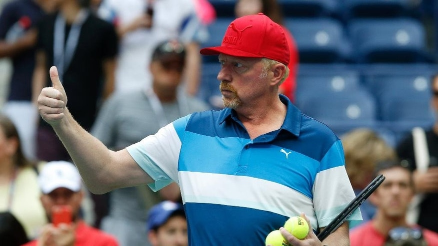 Boris Becker motions as he watches Novak Djokovic, of Serbia, practice after his opponent, Mikhail Youzhny, of Russia, retired in the first set of their match during the third round of the U.S. Open tennis tournament, Friday, Sept. 2, 2016, in New York. (AP Photo/Jason DeCrow)