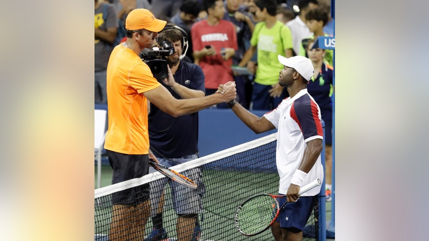 Donald Young, right, of the United States, shakes hands with Ivo Karlovic, of Croatia, after Karlovic won their match during the U.S. Open tennis tournament, Thursday, Sept. 1, 2016, in New York. (AP Photo/Julio Cortez)