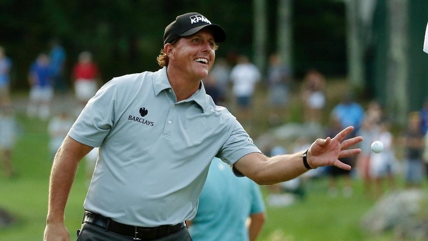 Phil Mickelson tosses the ball to his caddie after putting out on the 18th hole during the first round of the Deutsche Bank Championship golf tournament in Norton, Mass., Friday, Sept. 2, 2016. (AP Photo/Michael Dwyer)
