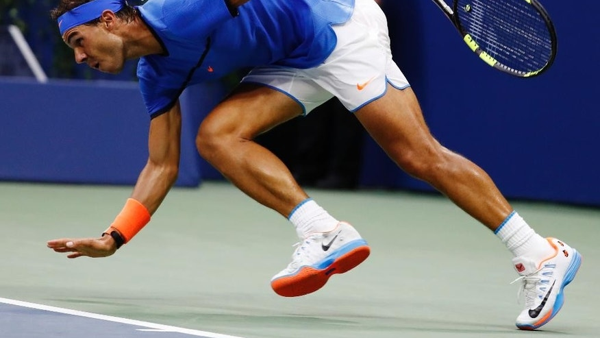 Rafael Nadal, of Spain, struggles to maintain his footing during play against Lucas Pouille, of France, during the fourth round of the U.S. Open tennis tournament, Sunday, Sept. 4, 2016, in New York. (AP Photo/Alex Brandon)