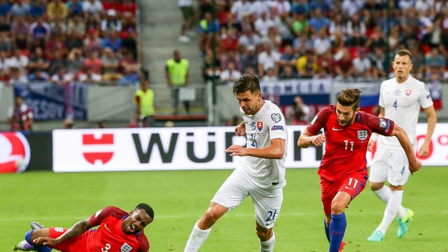 Slovakia's Michal Duris, center, challenges for a ball with England's Adam Lallana, right, as Danny Rose, left, falls down during their World Cup Group F qualifying soccer match in Trnava, Slovakia on Sunday Sept. 4, 2016. (AP Photo/Bundas Engler)