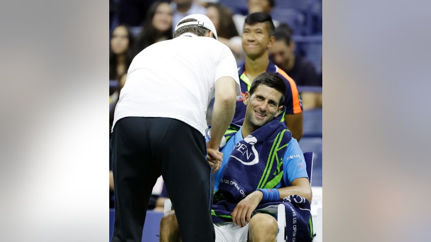 Novak Djokovic, of Serbia, receives medical attention during his match against Kyle Edmund, of Britain, in the fourth round of the U.S. Open tennis tournament, Sunday, Sept. 4, 2016, in New York. (AP Photo/Darron Cummings)