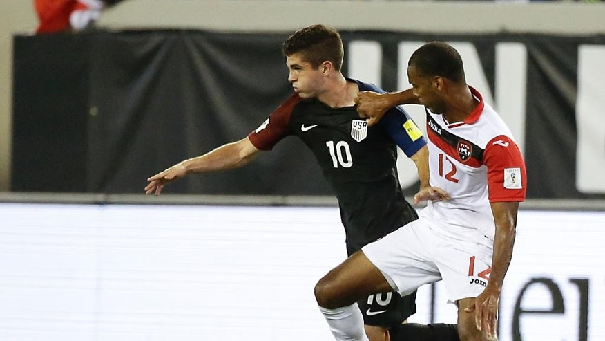 United States' Christian Pulisic (10) and Trinidad & Tobago's Carlyle Mitchell (12) battle for the ball during the first half of a CONCACAF World Cup qualifying soccer match, Tuesday, Sept. 6, 2016, in Jacksonville, Fla. (AP Photo/John Raoux)