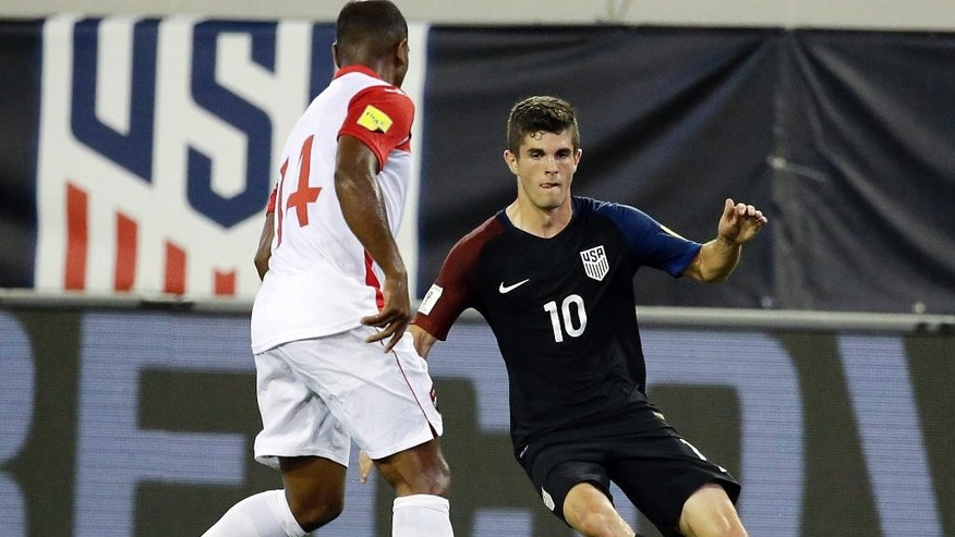 United States' Christian Pulisic (10) tries to moves the ball around Trinidad & Tobago's Andre Boucaud (14) during the first half of a CONCACAF World Cup qualifying soccer match, Tuesday, Sept. 6, 2016, in Jacksonville, Fla. (AP Photo/John Raoux)