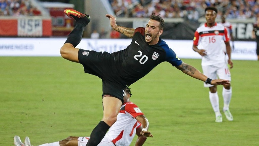 United States' Geoff Cameron (20) is fouled by Trinidad & Tobago's Mekeil Williams, bottom, during the first half of a CONCACAF World Cup qualifying soccer match, Tuesday, Sept. 6, 2016, in Jacksonville, Fla. (AP Photo/John Raoux)