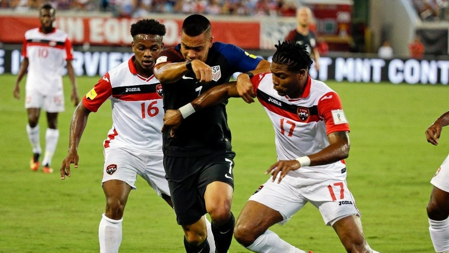 United States' Bobby Wood (7) gets between Trinidad & Tobago's Levi Garcia (16) and Mekeil Williams (17) as he goes for the ball during the first half of a CONCACAF World Cup qualifying soccer match, Tuesday, Sept. 6, 2016, in Jacksonville, Fla. (AP Photo/John Raoux)