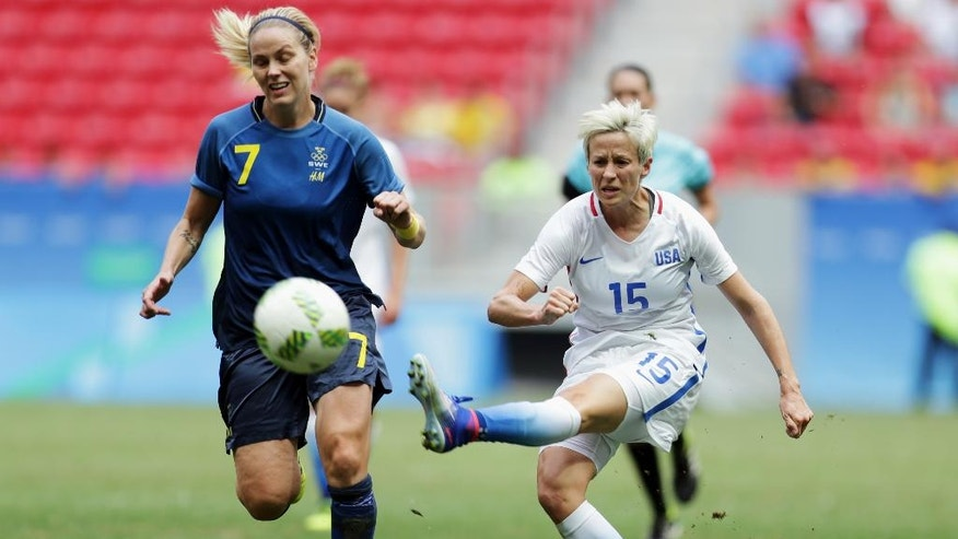 "FILE - In this Friday, Aug. 12, 2016, file photo, United States' Megan Rapinoe, right, kicks the ball past Sweden's Lisa Dahlkvist during a quarterfinal match of the women's Olympic soccer tournament in Brasilia. Rapinoe knelt during the national anthem Sunday, Sept. 4, before the Seattle Reign's game against the Chicago Red Stars ""in a little nod"" to NFL quarterback Colin Kaepernick. (AP Photo/Eraldo Peres, File)"
