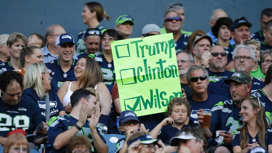 A Seattle Seahawks fan holds a sign suggesting Seahawks quarterback Russell Wilson for U.S. president, instead of Hillary Clinton or Donald Trump, during the Seahawks' preseason NFL football game against the Minnesota Vikings, Thursday, Aug. 18, 2016, in Seattle.