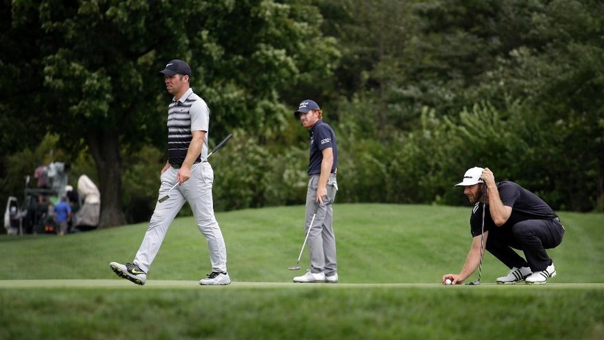 Dustin Johnson, right, Roberto Castro, center, and Paul Casey look over the putting green on the seventh hole during the third round of the BMW Championship golf tournament at Crooked Stick Golf Club in Carmel, Ind., Saturday, Sept. 10, 2016. (AP Photo/AJ Mast)