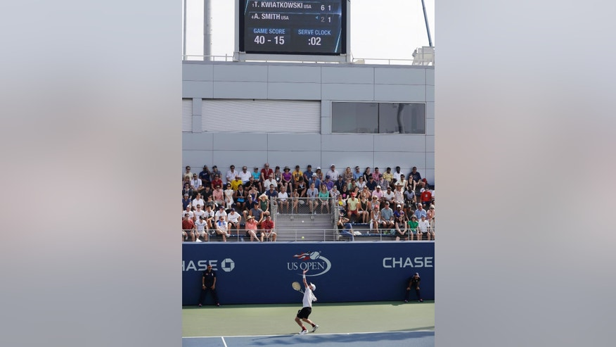 Thai-Son Kwiatkowski, of the United States, serves to Austin Smith, of the United States, during the men's collegiate invitational final of the U.S. Open tennis tournament, Saturday, Sept. 10, 2016, in New York. Above is the 20-second serve clock that was used this year at the U.S. Open's junior and college invitational tournaments. (AP Photo/Darron Cummings)