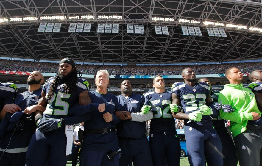 Seattle Seahawks players and coaches, including cornerback Richard Sherman (25) and head coach Pete Carroll, third from left, stand and link arms during the singing of the national anthem before an NFL football game against the Miami Dolphins, Sunday, Sept. 11, 2016, in Seattle. (AP Photo/Elaine Thompson)