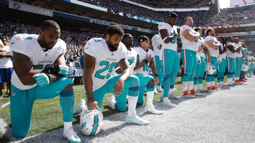 Jelani Jenkins, left, Arian Foster, Michael Thomas and Kenny Stills kneel during the National Anthem.