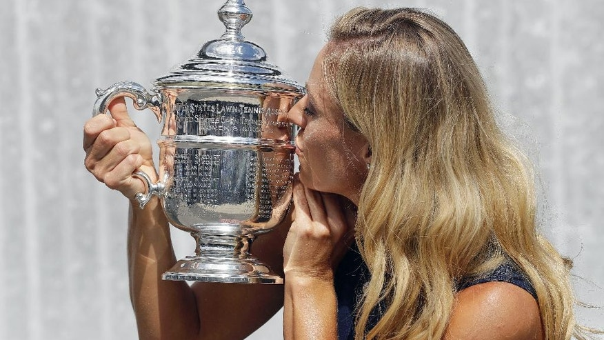 Angelique Kerber, of Germany, poses with the championship trophy after winning the women's single final at the U.S. Open tennis tournament, Sunday, Sept. 11, 2016, in New York. (AP Photo/Darron Cummings)
