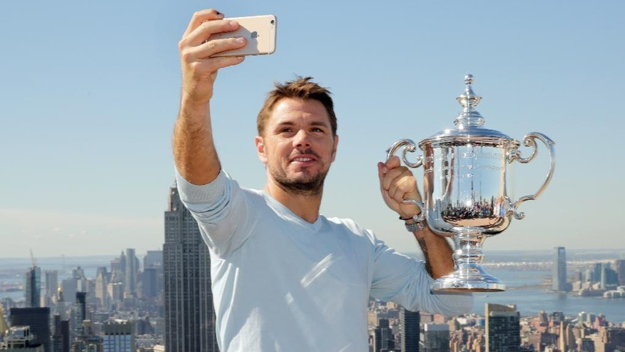 "U.S. Open men's singles tennis champion Stan Wawrinka takes a selfie picture as he poses for photos at the ""Top of the Rock,"" in New York's Rockefeller Center, Monday, Sept. 12, 2016. Wawrinka wore down Novak Djokovic and beat the defending champion 6-7 (1), 6-4, 7-5, 6-3 on Sunday for his first U.S. Open title and third Grand Slam trophy overall. (AP Photo/Richard Drew)"
