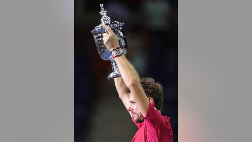 Stan Wawrinka, of Switzerland, holds up the championship trophy after winning the men's singles final of the U.S. Open tennis tournament over Novak Djokovic, of Serbia, Sunday, Sept. 11, 2016, in New York. (AP Photo/Charles Krupa)