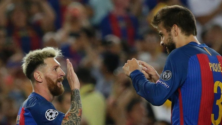 Barcelona's Lionel Messi, left, celebrates scoring his side's 5th goal and his hat trick with Gerard Pique during a Champions League, Group C soccer match between Barcelona and Celtic, at the Camp Nou stadium in Barcelona, Spain, Tuesday, Sept. 13, 2016. (AP Photo/Emilio Morenatti)