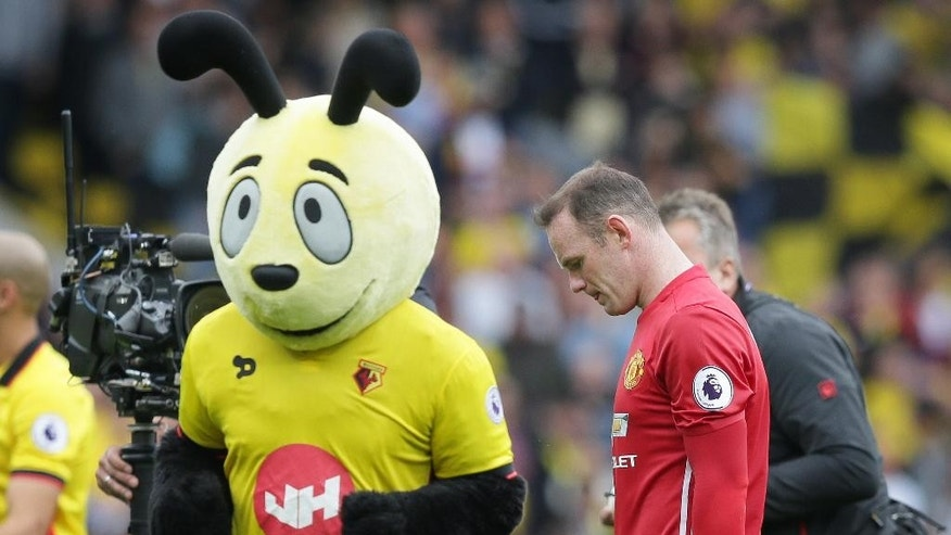 Manchester United's Wayne Rooney walks from the pitch past the Watford team mascot 'Harry the Hornet' after losing the English Premier League soccer match between Watford and Manchester United at Vicarage Road in London, Sunday Sept. 18, 2016. (AP Photo/Tim Ireland)
