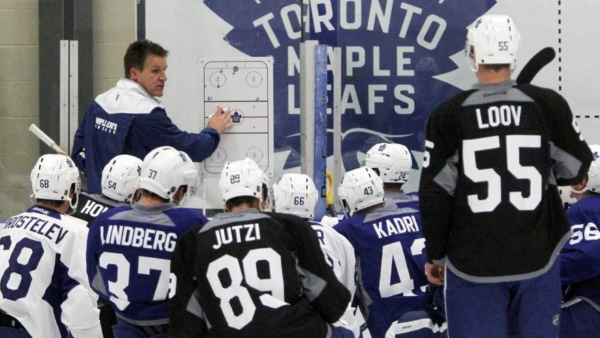 Toronto Maple Leafs' assistant coach Jim Hiller, left, instructs players during NHL training camp at the BMO Centre in Halifax, Nova Scotia, Friday, Sept. 23, 2016. (The Canadian Press via AP)