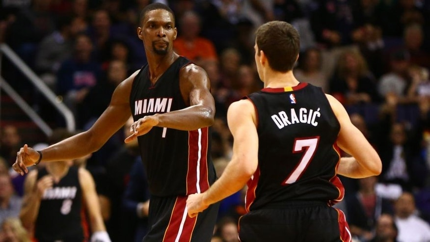 Jan 8, 2016; Phoenix, AZ, USA; Miami Heat center Chris Bosh (1) celebrates a play with guard Goran Dragic (7) against the Phoenix Suns at Talking Stick Resort Arena. The Heat defeated the Suns 103-95. Mandatory Credit: Mark J. Rebilas-USA TODAY Sports