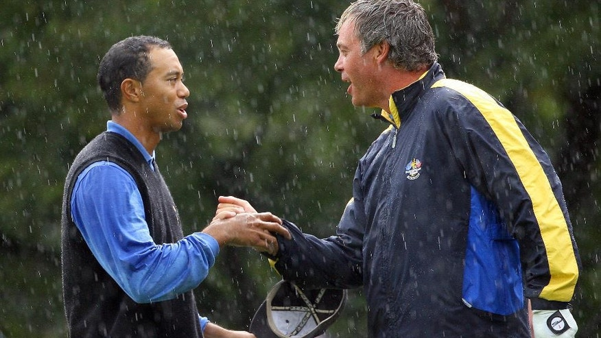 FILE - In this sept. 23, 2006, file photo, Europe's Darren Clarke, right, is congratulated by Tiger Woods, of the United States, on the 16th green after Clarke and Lee Westwood won their fourball match against Woods and Jim Furyk by 3 and 2 on the second day of the 2006 Ryder Cup at the K Club golf course, Straffan, Ireland. Clarke knows his way around the spotlight. Europe's Ryder Cup captain won only one major as a player, but was often at his best when it mattered most. (AP Photo/Laurent Rebours, FIle)