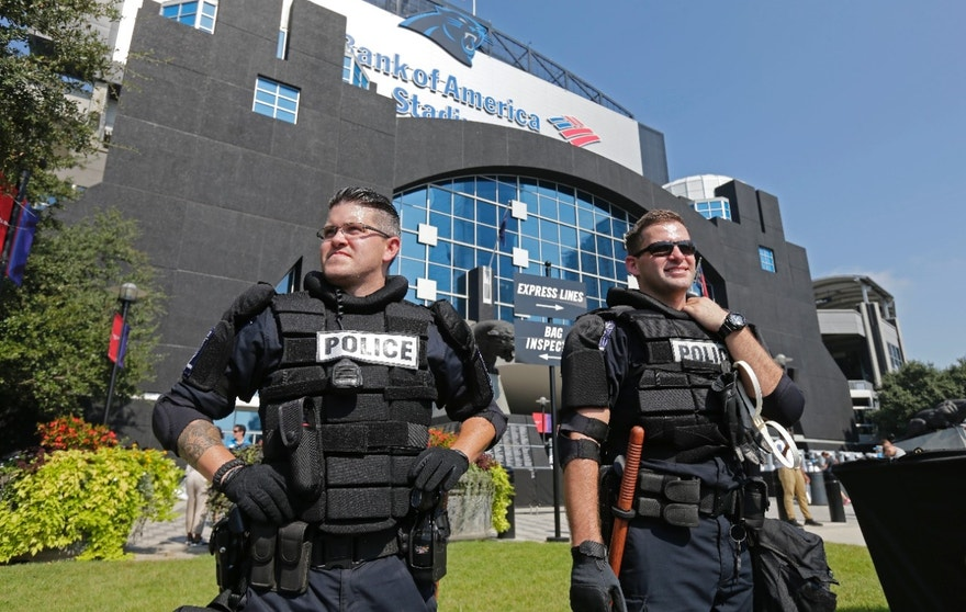 Charlotte-Mecklenburg Police officers stand guard outside Bank of America Stadium before an NFL football game between the Carolina Panthers and the Minnesota Vikings in Charlotte, N.C., Sunday, Sept. 25, 2016. Increased security is in place for the game after five nights of protests over Tuesday's fatal police shooting of Keith Lamont Scott. (AP Photo/Chuck Burton)