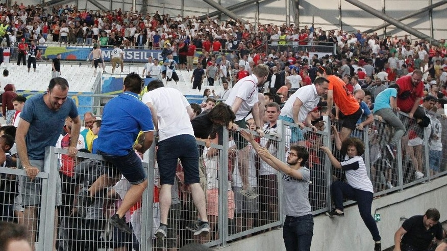 FILE- In this Saturday, June 11, 2016 file photo, spectators run on the stands as clashes break out right after the Euro 2016 Group B soccer match between England and Russia, at the Velodrome stadium in Marseille, France. Russian police are readying for Tottenham Hotspur's game against CSKA Moscow next Tuesday, Sept. 27, 2016 the first visit by an English club to Russia since clashes between the two countries' fans marred the European championship, though a repeat of that mass violence appears unlikely. (AP Photo/Thanassis Stavrakis, File)