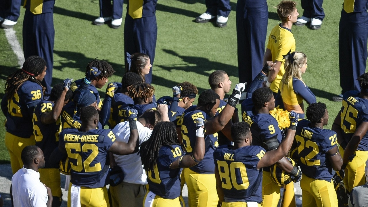Michigan football players raise their fists up in protest during the National Anthem, before an NCAA college football game against Penn State, Saturday, Sept. 24, 2016, in Ann Arbor, Mich.  (Junfu Han/The Ann Arbor News via AP)