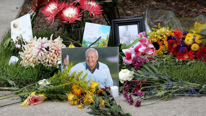 Flowers and mementos adorn a makeshift memorial honoring the late golf great Arnold Palmer at Palmer's parking spot at the Golf Channel studios  in Orlando, Fla., Monday, Sept. 26, 2016. Palmer died Sunday in Pittsburgh. (Joe Burbank/The Orlando Sentinel)