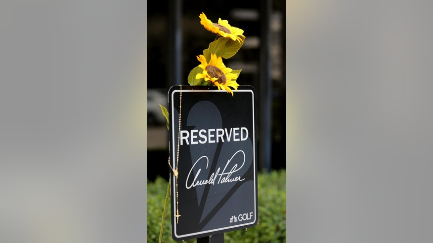 Flowers and Rosary beads at the makeshift memorial honoring golf legend Arnold Palmer,  at Palmer's parking spot at the Golf Channel studios, in Orlando, Fla. Monday, September 26, 2016. Palmer died Sunday in Pittsburgh. (Joe Burbank/Orlando Sentinel via AP)