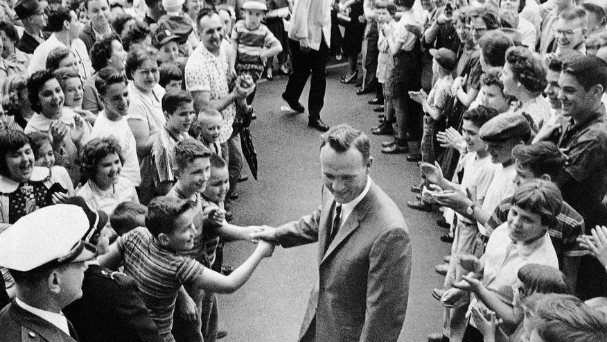 "File-This April 16, 1960, file photo shows a grinning Arnold Palmer surrounded by applauding citizens of his native Latrobe,Pa., shaking hands with a couple of enthusiastic boys. Palmer, who made golf popular for the masses with his hard-charging style, incomparable charisma and a personal touch that made him known throughout the golf world as ""The King,"" died Sunday, Sept. 25, 2016, in Pittsburgh. He was 87.  (AP Photo/File)"