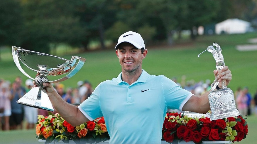 Rory McIlroy poses with the trophies after winning the Tour Championship golf tournament and FedEX Cup at East Lake Golf Club, Sunday, Sept. 25, 2016, in Atlanta. (AP Photo/John Bazemore)