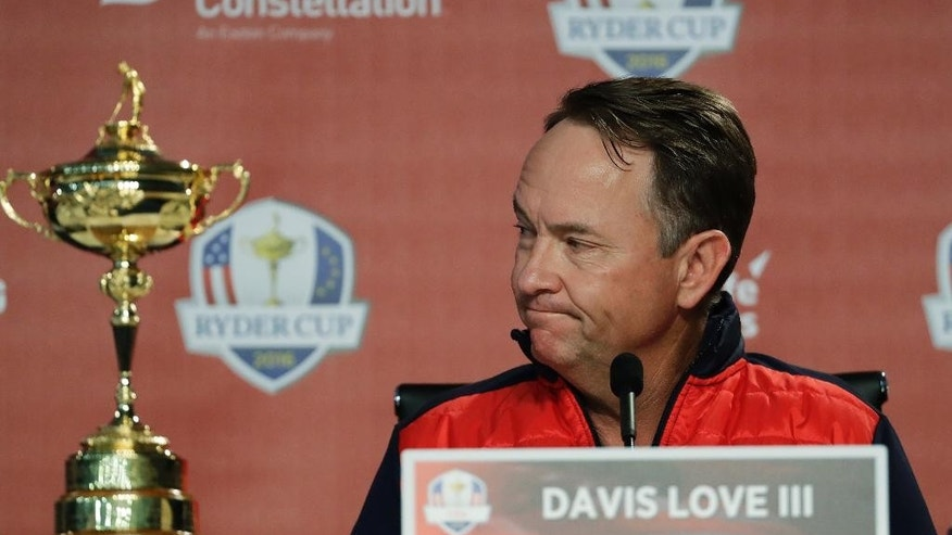 United States captain Davis Love III listens to the PGA president talk about Arnold Palmer before a press conference for the Ryder Cup golf tournament Monday, Sept. 26, 2016, at Hazeltine National Golf Club in Chaska, Minn. (AP Photo/David J. Phillip)