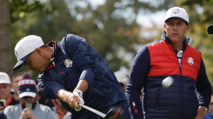 United States' Phil Mickelson watches as United States' Rickie Fowler drives on the sixth hole during a practice round for the Ryder Cup golf tournament Tuesday, Sept. 27, 2016, at Hazeltine National Golf Club in Chaska, Minn. (AP Photo/Chris Carlson)